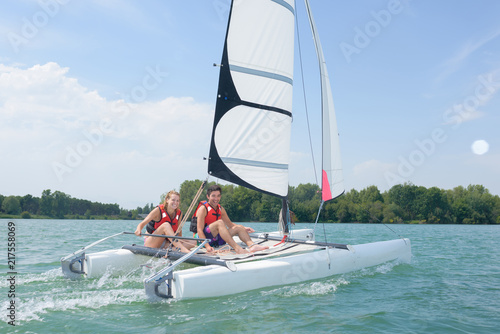 Foto young couple steering a catamaran