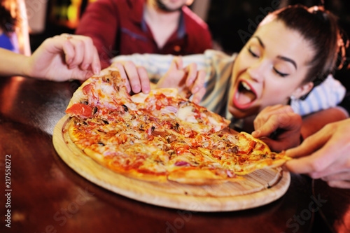 Appetizing hot pizza closeup on a table in the background of a group or company of people friends