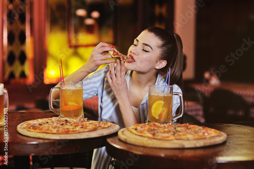 a young pretty girl eating pizza and drinking beer or a beer citrus cocktail on the background of a bar or pizzeria.