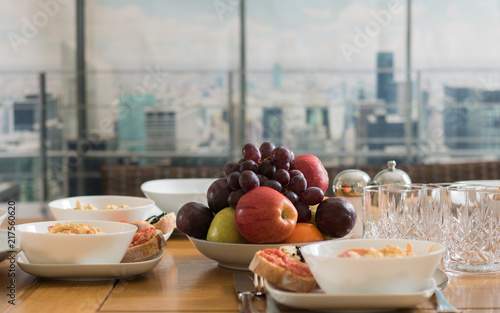 Wooden table with a meal is on a background of a window overlooking a city Canvas Print