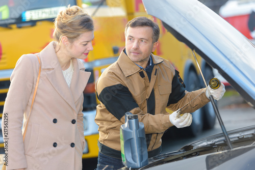 Fototapeta Recovery driver checking oil in woman's car obraz