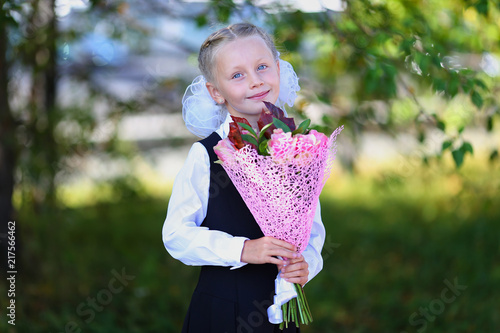 Portrait of a happy school girl in a uniform with bouquet of flowers. Back to school outdoors