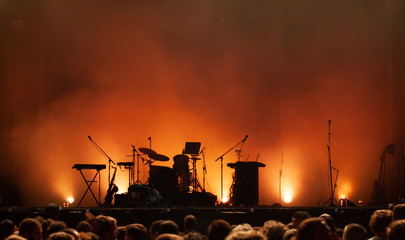 empty concert stage on music festival, instruments silhouettes, microphones drums guitars and crowd of people