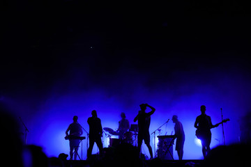 music band playing on concert stage, silhouettes of musicians unrecognizable, group of people singing together in rock festival