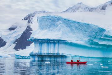 zimski kajak na Antarktiku, ekstremna sportska avantura, ljudi veslaju kajakom u blizini sante leda