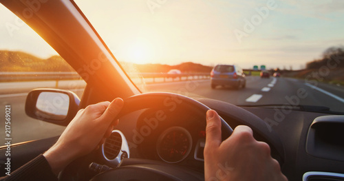 Vászonkép hands of car driver on steering wheel, road trip, driving on highway road