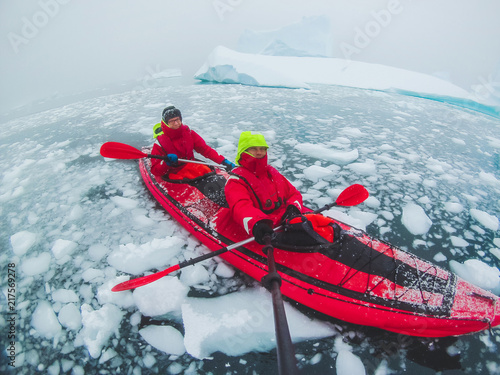 Valokuvatapetti kayaking in Antarctica, couple of kayakers doing travel selfie with icebergs, ex