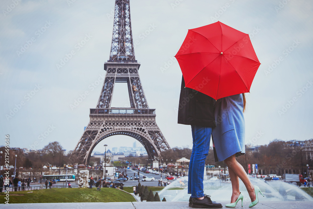 Fototapeta romantic holidays for couple in Paris, honeymoon vacation in France, Europe, man and woman kissing near Eiffel tower
