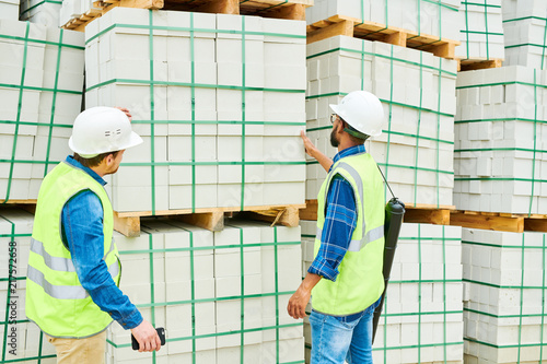 Fotografia, Obraz  Back view of two men in helmets and waistcoats looking at stack of building mate