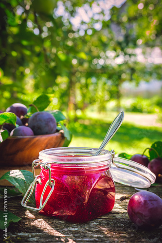 Glass jar with plum jam confiture and ripe plum berries in a basket on a wooden vintage table in the garden with a copy space, the idea of home canning and organic ecological bio nutrition