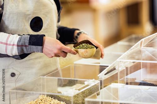 Fotografie, Obraz  Saleswoman putting soya in a bulk shopping bag in an organic store