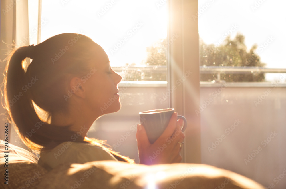Fototapeta Girl enjoying morning coffee in living room