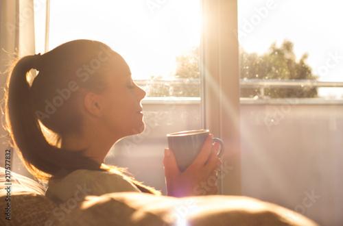 Obraz Girl enjoying morning coffee in living room - fototapety do salonu