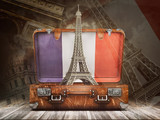 Fototapeta Fototapety z wieżą Eiffla - Trip to Paris. Travel or tourism to France concept. Eiffel tower andvintage suitcase with flag of France on the map of world background