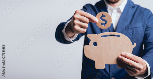 Fototapeta Businessman holds a coin under wooden piggy. Money box. Collecting money with earning bank. obraz