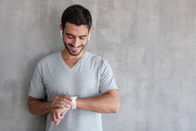 Young Handsome Man Wearing Wireless Headphones And T Shirt, Checking Smart Watches With Touch Screen, Standing Against Gray Textured Wall With Copy Space