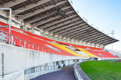 Plakat Puste pomarańcze i koloru żółtego siedzenia przy stadium, wiosłują przejście siedzenie na stadium piłkarskim
