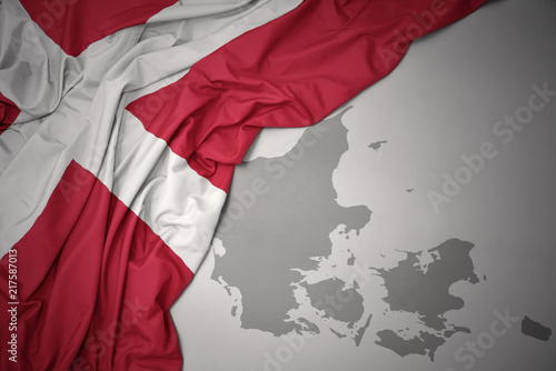 Photo  waving colorful national flag and map of denmark.