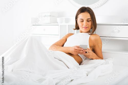 Fotobehang Akt Woman using phone in bed
