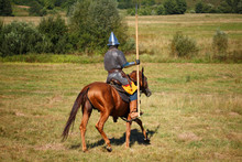 Medieval Armored Knight Whith Lance On Horse. Equestrian Soldier In Historical Costume. Reenactor Is In The Field