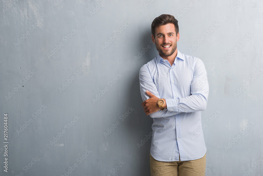 Fototapeta Handsome young business man over grey grunge wall wearing elegant shirt happy face smiling with crossed arms looking at the camera. Positive person.