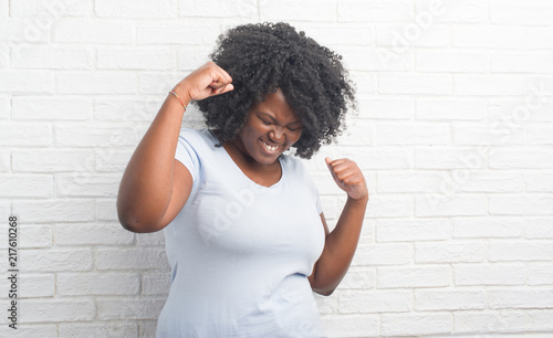 Photo  Young african american plus size woman over white brick wall very happy and excited doing winner gesture with arms raised, smiling and screaming for success