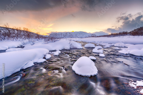 Tuinposter Purper Water stream with rocks in a winter landscape in twilight.