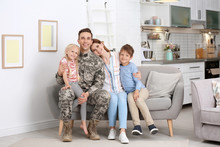 Man In Military Uniform With His Family On Sofa At Home