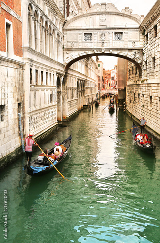 Foto op Canvas Venice Gondolier carrying tourists in their gondola, by the bridge of sighs in venice, italy at sunset