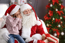 Little Girl Whispering In Authentic Santa Claus' Ear Indoors