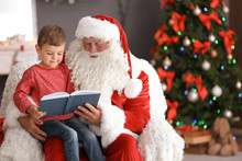 Little Boy Reading Book While Sitting On Authentic Santa Claus' Lap Indoors