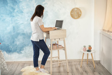 Young Woman Using Laptop At Stand Up Workplace In Room