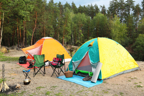 Fototapeta Camping tents and accessories in wilderness on summer day