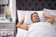 canvas print picture - Man covering ears with pillow while trying to sleep in bed at home