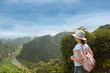 woman tourist with backpack enjoying valley view from top of a mountain