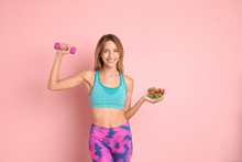 Happy Slim Woman In Sportswear With Salad And Dumbbell On Color Background. Weight Loss Diet