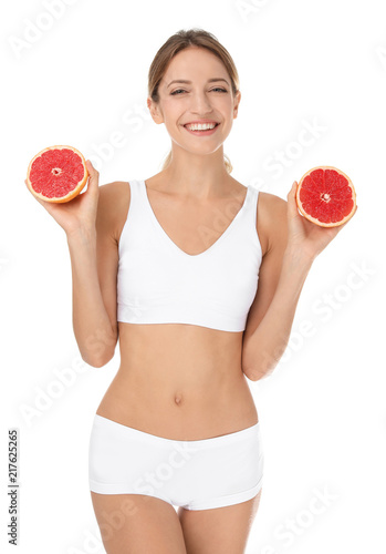 Happy slim woman in underwear holding grapefruit on white background. Weight loss diet