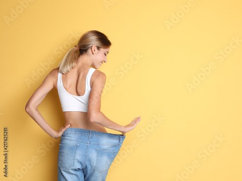 Young slim woman in old big jeans showing her diet results on color background Fotobehang