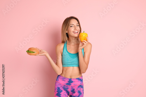 Young woman with burger and bell pepper on color background. Choice between diet and unhealthy food