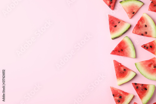 Slices of ripe watermelon on color background, top view with space for text
