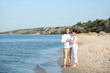 Happy mature couple at beach on sunny day
