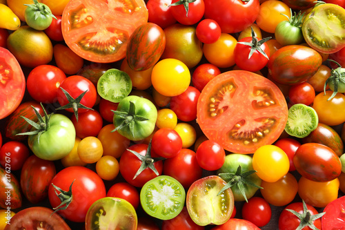 Different sorts of tomatoes as background, closeup