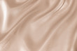 The texture of the satin fabric of beige color for the background