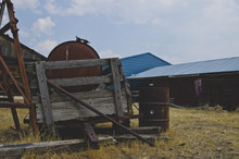 The Old Rusty Tools And Equipment On The Farm Under The Summer Sun.