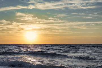 Fototapeta Vintage Seascape - the sun at the horizon of the stormy sea at dawn