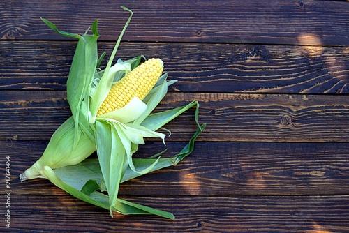 Staande foto Lelietje van dalen A cob of sweet corn in a husk on a wooden background. Top view, copy space.