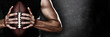 Leinwandbild Motiv Football player man player holding american football on black blackboard texture background with copy space for text or design. Panoramic banner.