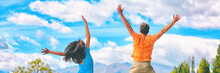 Happy People Jumping Of Fun Enjoying Travel Adventure. Young Couple From Behind Happiness Jump Banner Panorama In Blue Sky.