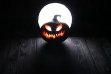 Halloween Scary Pumpkin Jack-o-lantern On The Dark Wooden Background