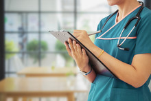 Female Doctor Hold Clipboard Pad And Fill Medical History List At Workplace.